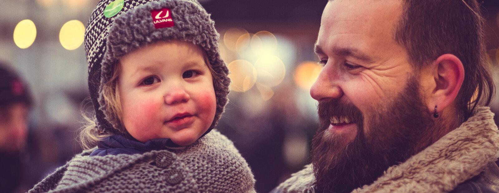 Glad mann med et barn.
